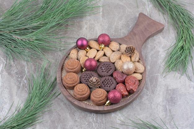 Ein holzbrett von mandeln und keksen auf marmorhintergrund. Kostenlose Fotos