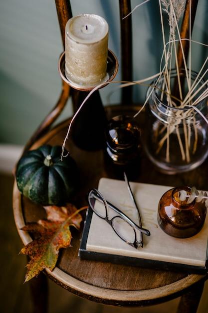 Ein holztisch, der mit einem herbstmotiv dekoriert ist und eine aromatische kerze, gläser, trockenblumen, Kostenlose Fotos