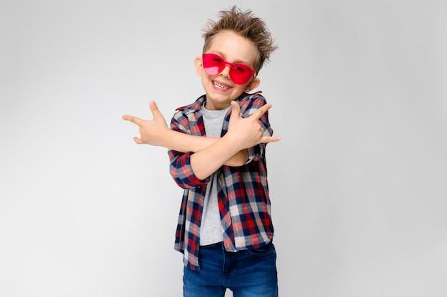 Ein hübscher junge in einem karierten hemd, in einem grauen hemd und in jeans steht auf grau Premium Fotos