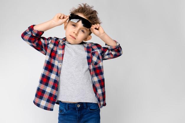 Ein hübscher junge in einem karierten hemd, in einem grauen hemd und in jeans steht. der junge mit der schwarzen sonnenbrille. der junge hält seine brille. Premium Fotos