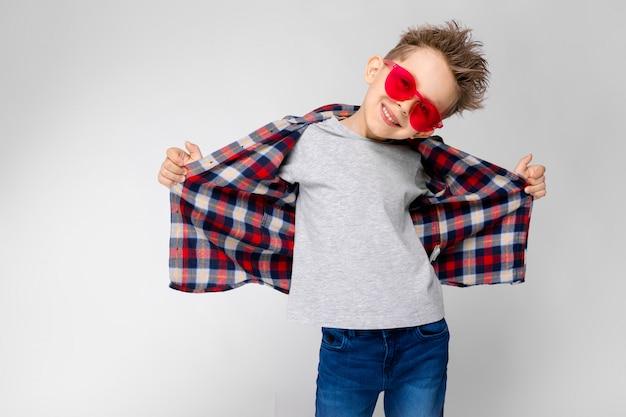 Ein hübscher junge in einem karierten hemd, in einem grauen hemd und in jeans steht Premium Fotos