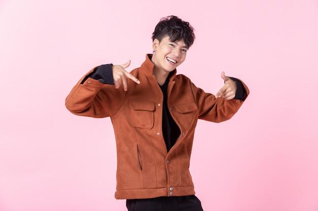 Ein hübscher junger mann auf einem rosa hintergrund Premium Fotos
