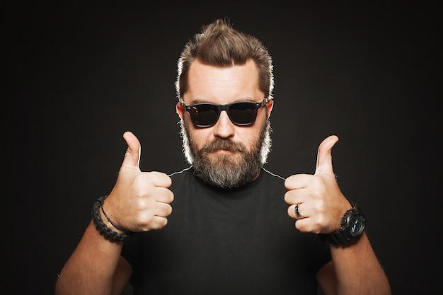 Ein hübscher, starker mann zeigt zwei daumen nach oben. Premium Fotos