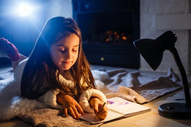 Ein hübsches kleines mädchen buch auf dem boden unter der lampe. kinder und bildung. Premium Fotos