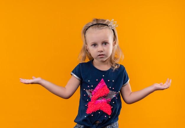 Ein hübsches kleines mädchen, das ein dunkelblaues hemd im kronenstirnband trägt, das überraschend mit offenen armen auf einer orange wand sieht Kostenlose Fotos