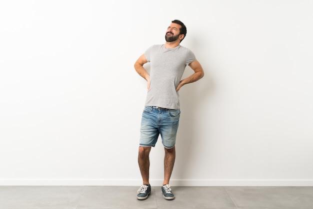 Ein in voller länge schuss des gutaussehenden mannes mit dem bart, der unter rückenschmerzen leidet, weil er sich bemüht hat Premium Fotos