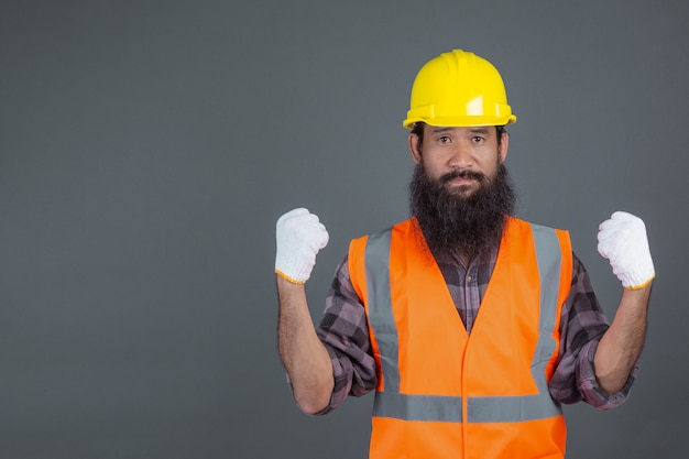 Ein ingenieur, der einen gelben helm mit weißen handschuhen trug, zeigte eine geste auf einem grau. Kostenlose Fotos