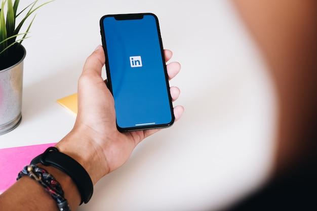 Ein iphone xs mit linkedin-anwendung auf dem bildschirm.linkedin ist eine app zum teilen von fotos für smartphones. Premium Fotos