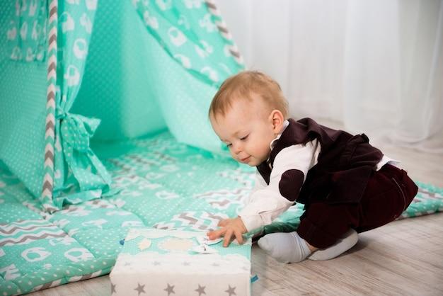 Ein jähriges fröhliches baby spielt zu hause. Premium Fotos