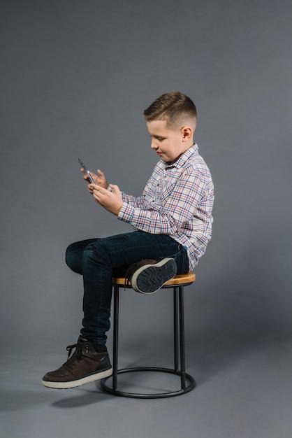 Ein junge, der auf schemel unter verwendung des handys gegen grauen hintergrund sitzt Kostenlose Fotos
