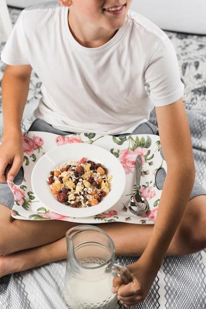 Ein junge, der mit behälter des hafers sitzt, blättert ab, milchglaskrug halten Kostenlose Fotos