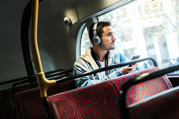 Ein junge hört musik in kopfhörern und benutzt das handy in einem bus Premium Fotos