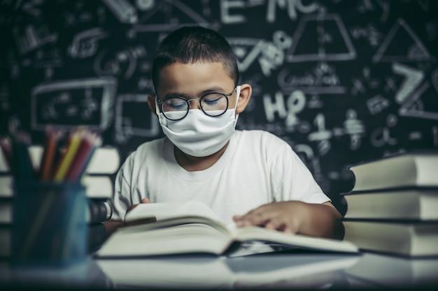 Ein junge mit brille sitzt im klassenzimmer und liest Kostenlose Fotos