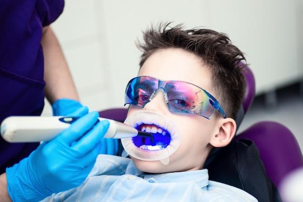 Ein junge mit schutzbrille auf dem zahnarztstuhl. Premium Fotos