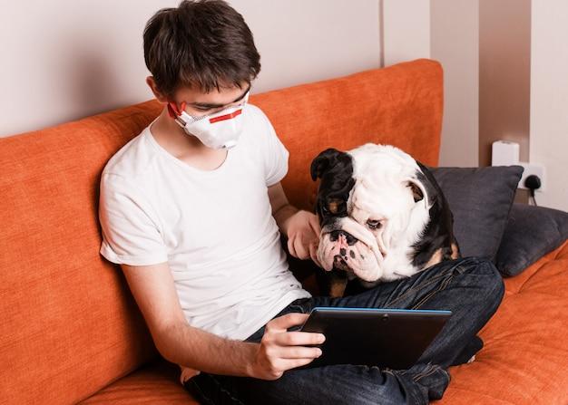 Ein junge sitzt auf einem sofa, trägt eine gesichtsmaske und lernt oder lernt online auf dem tablet mit seinem weißen und schwarzen hund Premium Fotos