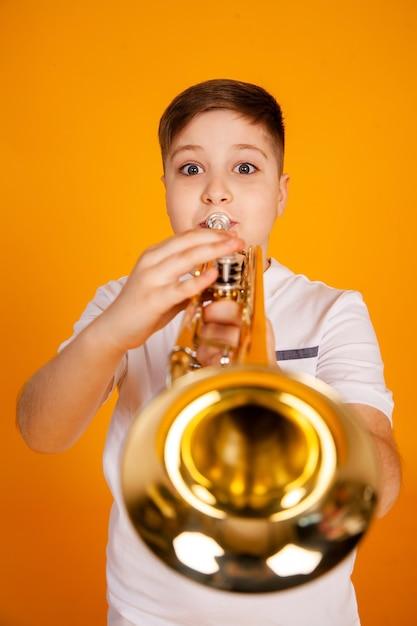 Ein junge spielt trompete. schöner teenager spielt trompetenmusikinstrument Premium Fotos