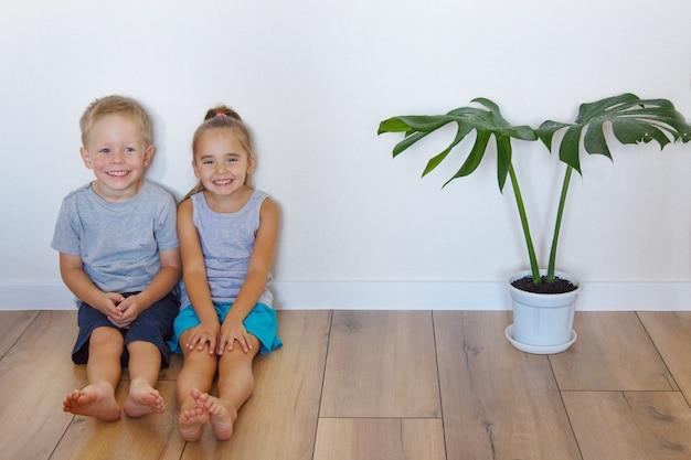 Ein junge und ein mädchen sitzen auf dem boden. kinder zusammen zu hause Premium Fotos
