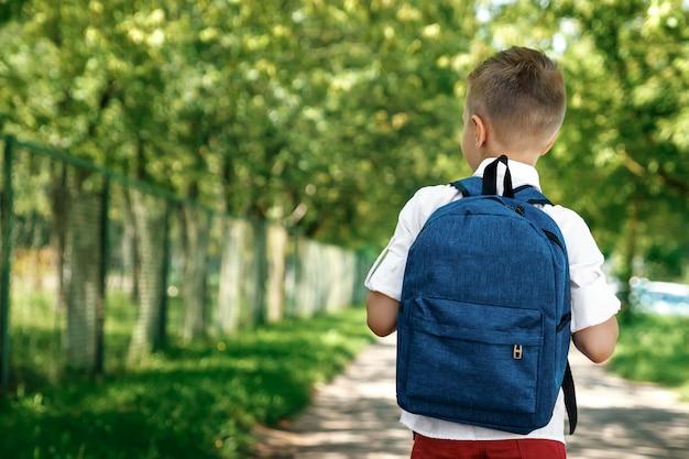 Ein junge von einer grundschule mit einem rucksack auf der straße Premium Fotos