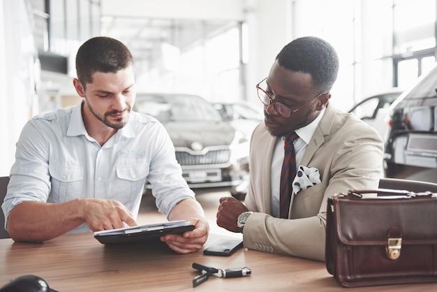Ein junger attraktiver schwarzer geschäftsmann kauft ein neues auto, unterschreibt einen vertrag und bringt die schlüssel zum manager. Kostenlose Fotos