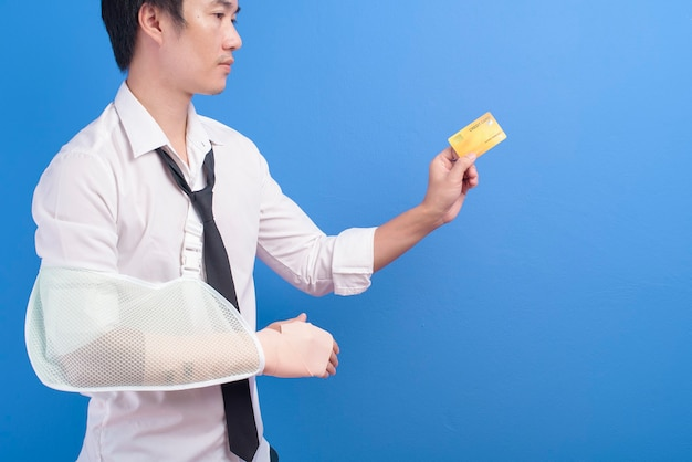 Ein junger geschäftsmann mit einem verletzten arm in einer schlinge, die eine kreditkarte oder eine krankenversicherungskarte über blauem hintergrund im studio-, versicherungs- und gesundheitskonzept hält Premium Fotos