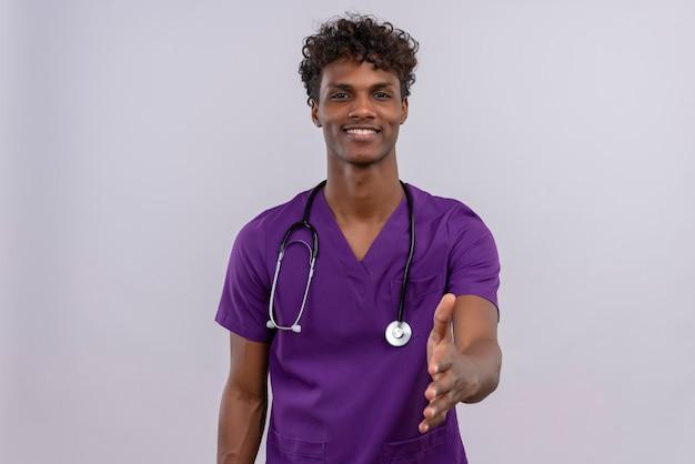 Ein junger gutaussehender dunkelhäutiger arzt mit lockigem haar in violetter uniform mit stethoskop streckender hand zum schütteln, um jemanden willkommen zu heißen oder hallo zu sagen Kostenlose Fotos