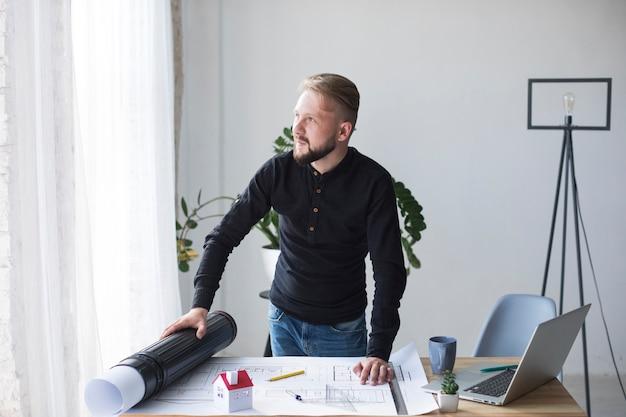 Ein junger männlicher architekt in seinem büro, das weg schaut Kostenlose Fotos