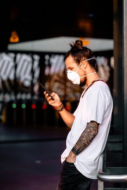 Ein junger mann, der die symptome des coronavirus in seinem telefon überprüft Premium Fotos