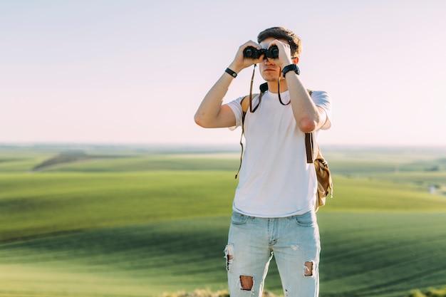 Ein junger mann, der durch binokulares gegen grasartiges land schaut Kostenlose Fotos