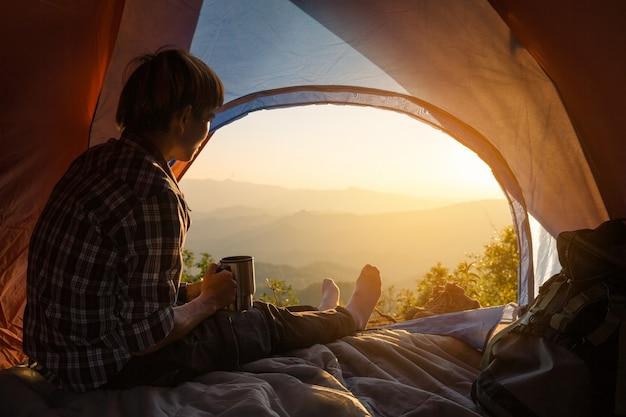 Ein junger mann, der im zelt mit dem halten der kaffeetasse sitzt Kostenlose Fotos