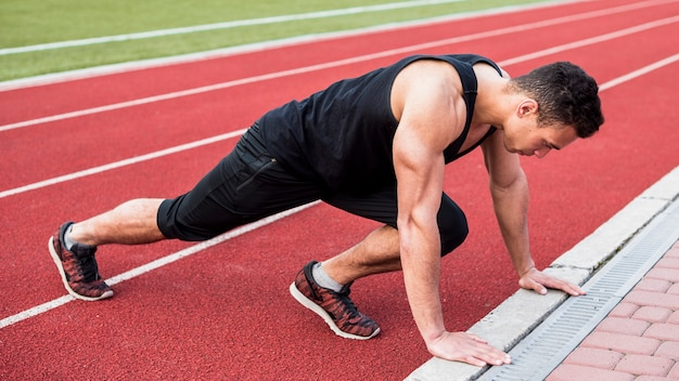 Ein junger mann der muskulösen eignung, der liegestütz auf roter laufbahn tut Kostenlose Fotos