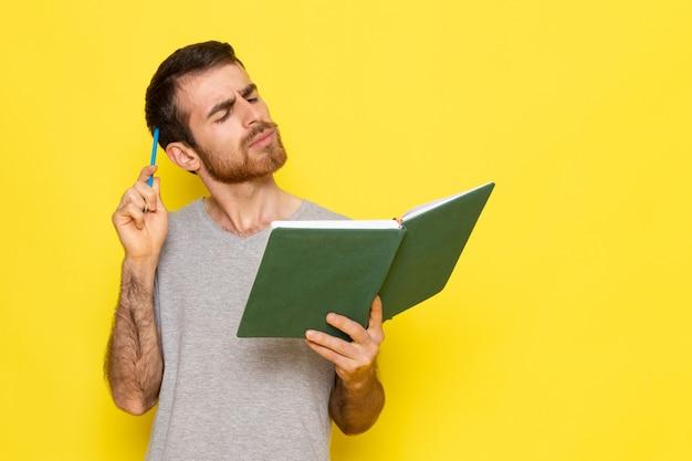 Ein junger mann der vorderansicht im grauen t-shirt-lesebuch mit denkendem ausdruck auf dem gelben wandmannausdruck-emotionsfarbmodell Kostenlose Fotos