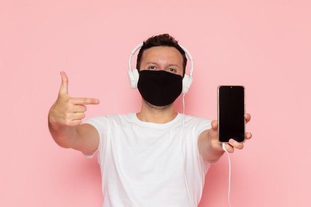 Ein junger mann der vorderansicht in der schwarzen maske des weißen t-shirts, die musik durch kopfhörer auf der farbemotionshaltung des rosa schreibtischmanns hört Kostenlose Fotos