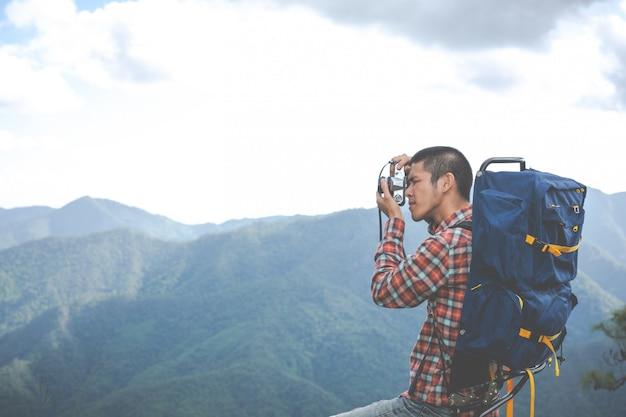 Ein junger mann fotografiert berggipfel in einem tropischen wald zusammen mit rucksäcken im wald. abenteuer, reisen, wandern. Kostenlose Fotos