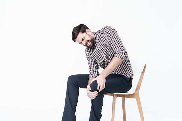 Ein junger mann hat schmerzen im bein. er massiert ein bein. Premium Fotos
