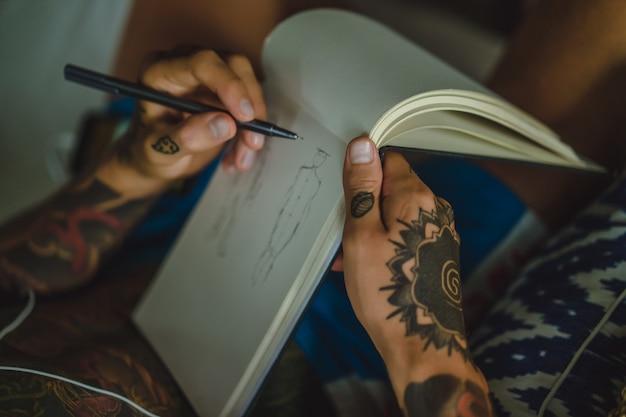 Ein junger mann in tattoos mit kopfhörern hört musik und zeichnet ein notizbuch. Kostenlose Fotos