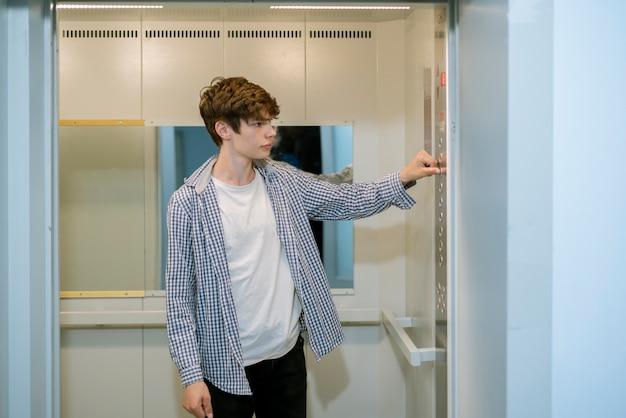 Ein junger mann in ungezwungener atmosphäre kommt in die aufzugskabine Premium Fotos