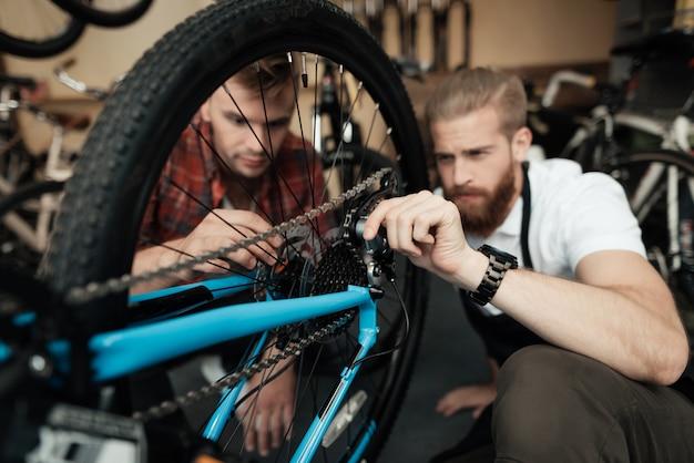 Ein junger mann kam in die werkstatt, um sein fahrrad zu reparieren Premium Fotos