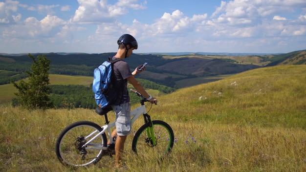 Ein junger mann mit dem fahrrad wird mithilfe einer karte auf seinem mobiltelefon durch das gelände geführt Premium Fotos