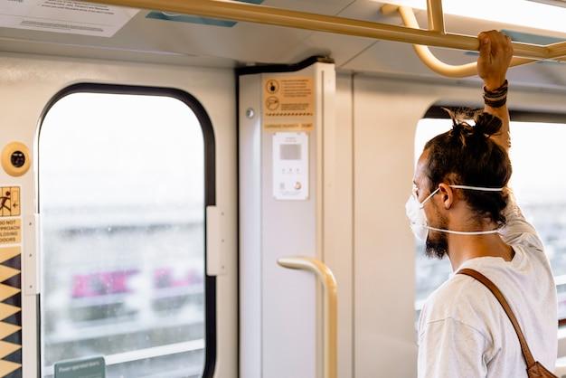 Ein junger mann mit einem brötchen trägt eine maske in der u-bahn Premium Fotos