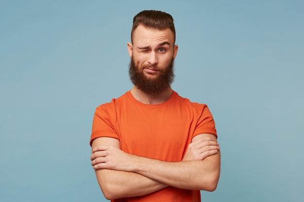 Ein junger mann mit einem schönen dicken bart gekleidet in einem roten t-shirt, das auf blau lokalisiert wird Kostenlose Fotos