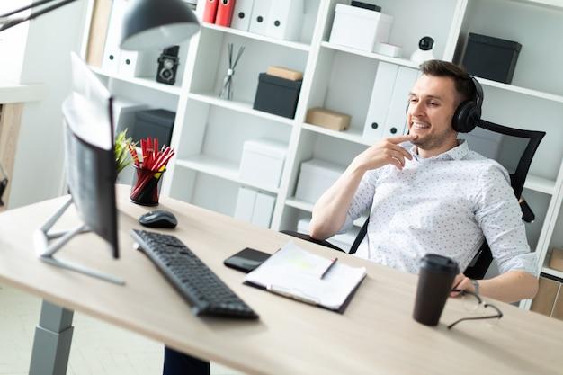 Ein junger mann mit kopfhörern sitzt an einem computertisch Premium Fotos