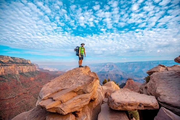 Ein junger mann mit offenen armen auf einem aussichtspunkt des abstiegs des south kaibab trailhead. grand canyon, arizona Premium Fotos