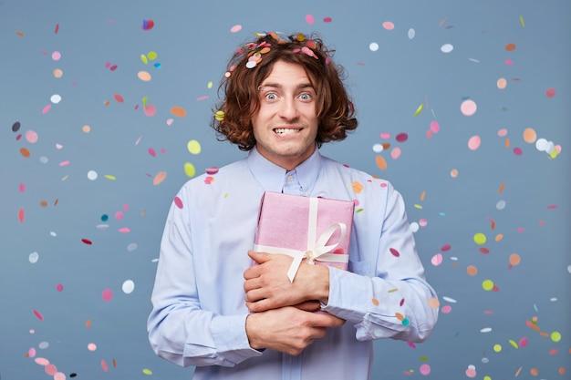 Ein junger mann steht mit einem ausdruck aus der geschenkbox im gesicht Kostenlose Fotos