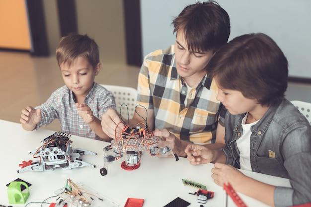 Ein junger mann und zwei kleine jungen sammeln roboter. Premium Fotos