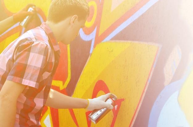 Ein junger rothaariger graffitikünstler malt ein neues graffiti an die wand Premium Fotos