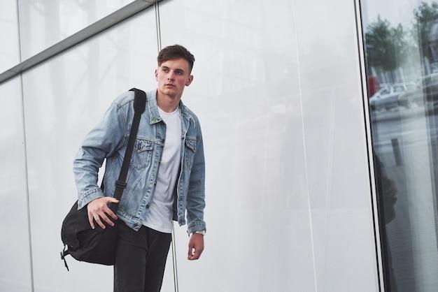 Ein junger schöner mann am flughafen wartet auf den flug. Kostenlose Fotos