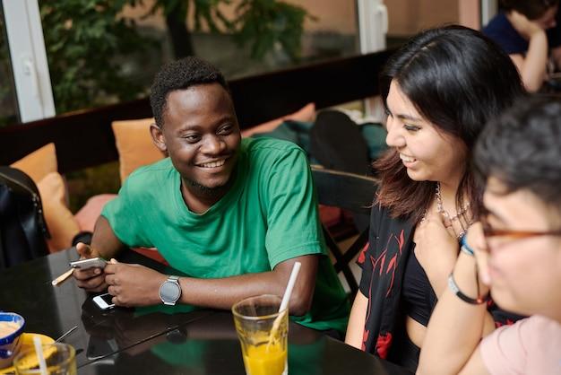 Ein junger schwarzer mann erzählt seiner freundin einen witz, umgeben von freunden in einem modernen café. Premium Fotos