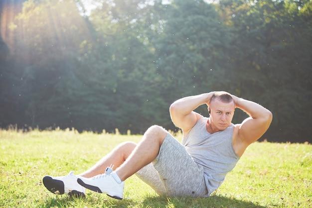 Ein junger sportler, der sich auf sport- und fitnesstraining im freien vorbereitet. Kostenlose Fotos
