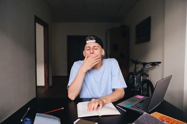 Ein junger student gähnt beim lesen eines buches. der student will schlafen. hausaufgaben. zu hause unterrichten. Premium Fotos
