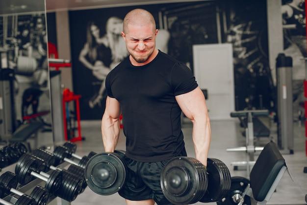 Ein junger und muskulöser kerl in einem schwarzen t-shirt bildet in einer turnhalle aus Kostenlose Fotos